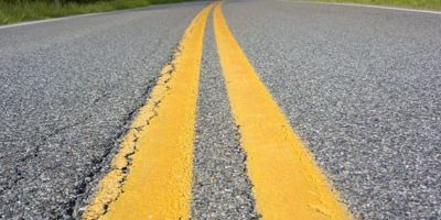Double solid yellow line markers on the center of a road.