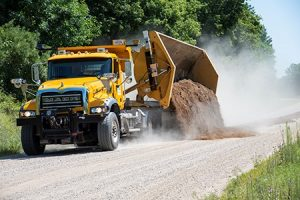 Side dumping plow truck on a gravel road