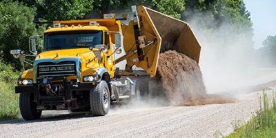Side dumping plow truck on a gravel road