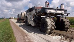 Truck incorporating cement into road materials on rural road.